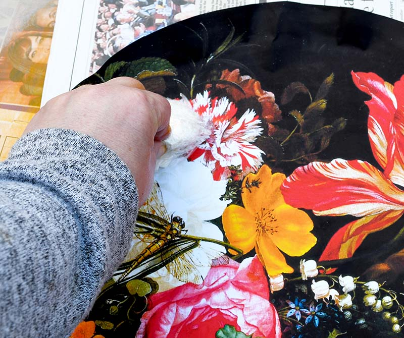 Smoothing out bubbles with flowers decoupage