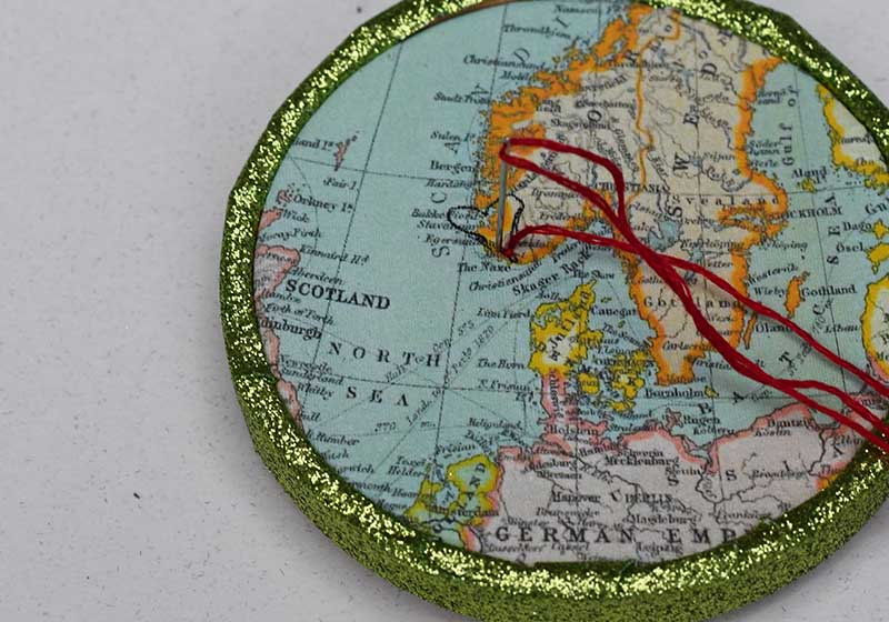 Embroidering the heart on the map ornaments